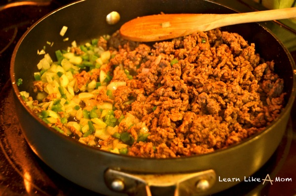 adding vegetables to the taco meat